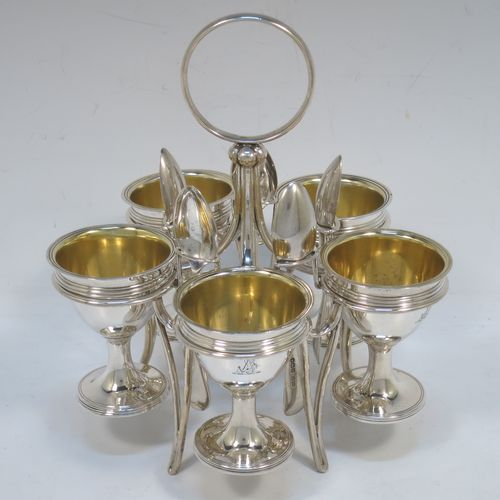 A very handsome Antique Victorian Sterling Silver egg cruet set, having five removable plain round egg cups with reeded borders and gold-gilt interiors, all sitting in a plain wire-work frame stand with five feet, together with five matching plain Old English pattern spoons. The cruet frame and egg cups made by the Barnard Brothers of London in 1859, and the spoons made by James Dixon and Sons of Sheffield in 1922. The dimensions of this fine hand-made antique silver egg cruet set are height 18 cms (7 inches), width 15 cms (6 inches), with a total weight of approx. 477g (15.4 troy ounces).