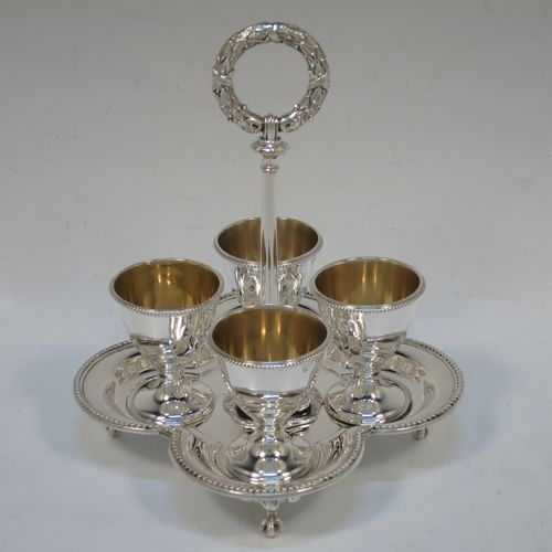 A very pretty Antique Victorian Sterling Silver egg cruet set, having four plain round egg cups with bead borders and gold-gild interiors sitting on pedestal feet, together with a cast laurel leaf loop handle attached to a lobed base with an applied bead-edged border, and all sitting on four cast claw and ball feet. Made by Elkington and Co., of Birmingham in 1866. The dimensions of this fine hand-made antique silver egg cruet set are height 18 cms (7 inches), width of base is 16.5 cms (6.5 inches), and the total weight is approx. 500g (16 troy ounces).