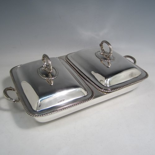Sterling silver pair of entree dishes with covers and handles, sitting in an original plain rectangular hot-water warming frame, with applied gadroon borders and hand-pierced liners, having cast side-handles, and all sitting on four cushion feet. Made by D. & J. Wellby of London in 1916. The dimensions of this fine hand-made silver entree dish set are length 36 cms (14 inches), width 20 cms (8 inches), height including cover handles 12 cms (4.75 inches), and it weighs a total of approx. 1,965g (63 troy ounces).
