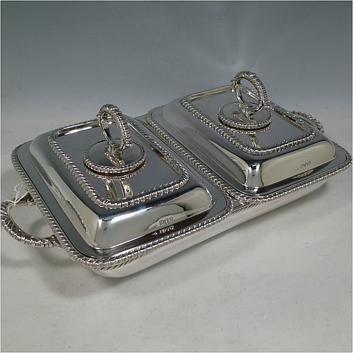 An Antique Edwardian Sterling Silver pair of entrée dishes with covers on a silver-plated warming stand for hot water, having rectangular bodies with applied gadroon borders, and with removable bayonet-fit handles. All in original condition and made by Goldsmiths & Silversmiths of London in 1902. The dimensions of this fine pair of hand-made antique silver entree dishes on a silver plated warming stand are length (inc. handles) 34 cms (13.5 inches), width 20 cms (8 inches), height 12 cms (5 inches), and the entree dishes weigh approx. 1,721g (55.5 troy ounces).