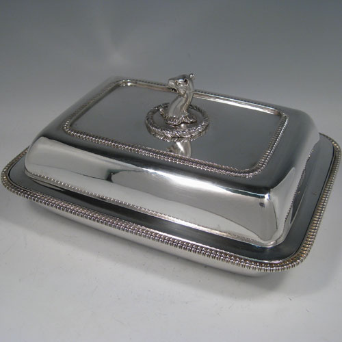 Antique Georgian sterling silver entree dish and cover, having a rectangular body, with gadroon edges, and removable cast leopards head handle. Made by John Foskett & John Stewart of London in 1809. The dimensions of this fine antique silver entree dish and cover are length 28 cms (11 inches), width 21.5 cms (8.5 inches), height including handle 12 cms (4.75 inches), and its wWeight is approx. 1,849g (59 troy ounces).