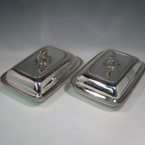 Antique Georgian pair of entree dishes with covers, having rectangular bodies with rounded corners, bayonet-fit removable gadroon and shell handles, gadroon borders, and sitting on flat bases. Made by Joseph Angell of London in 1817. The dimensions of this pair of fine hand-made antique silver entree dishes and covers are length 29 cms (11.5 inches), height including handle 13 cms (5 inches), width 21.5 cms (8.5 inches), and they weigh a total of approx. 3,120g (101 troy ounces). Please note that these are crested, and the Latin motto has been translated as The Moon Shall Fill Her Horns Again.