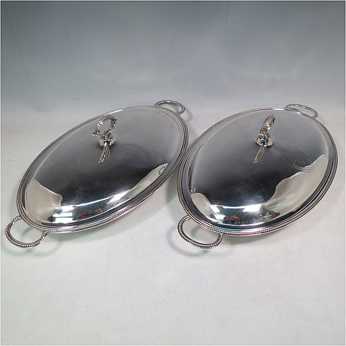 An Antique Georgian Sterling Silver pair of entree or hash dishes with covers, having oval bodies with applied bead-edged borders and cast loop side-handles, with plain domed lift-off covers having removable cast bead handles, and all sitting on flat bases. Made by Henry Green of London in 1790. The dimensions of this pair of fine hand-made antique silver entree dishes and covers are length 38 cms (15 inches), width 21.5 cms (8.5 inches), height including cover handle 11 cms (4.3 inches), and they weigh a total of approx. 2,077g (67 troy ounces). Please note that both the bases and covers are crested.