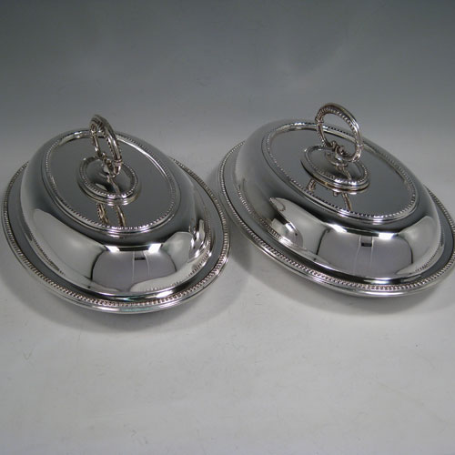 Sterling silver pair of entree dishes, having oval bodies, bead edges, and bayonet-fit removable loop handles. Made by Goldsmiths and Silversmiths of London in 1918. Length 25 cms (10 inches), width 18 cms (7 inches), height inc. handle 13 cms (5 inches). Total weight approx. 2,145g (69 troy ounces).
