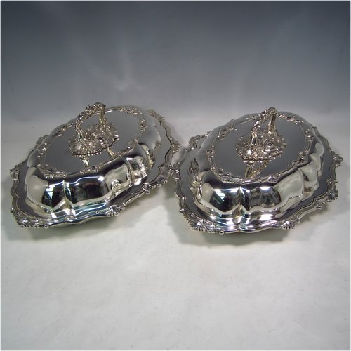 A Sterling Silver pair of entree dishes, having oval lobed bodies, with lift-off lids, removable bayonet-fit handles, applied cast floral and scroll borders, and sitting on flat bases. Made by James Dixon & Sons of Sheffield in 1918. The dimensions of this fine pair of hand-made silver entree dishes and covers are length 35 cms (13.75 inches), width 26 cms (10.25 inches), and they weigh a total of approx. 3,472g (112 troy ounces).