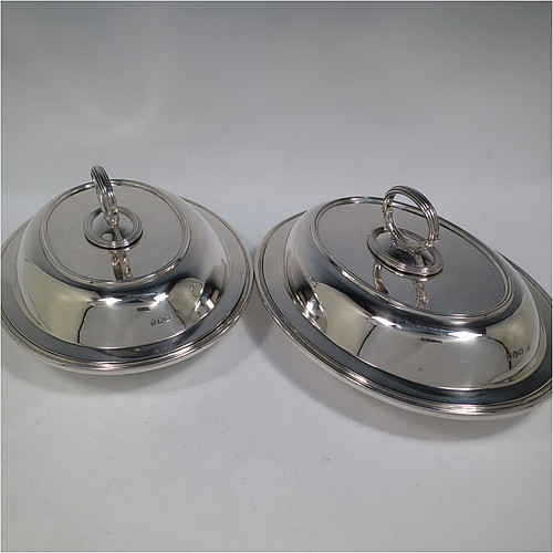 An Antique Victorian Sterling Silver pair of entree dishes, having plain oval bodies, with lift-off lids, removable bayonet-fit handles, applied reeded borders, and sitting on flat bases. Made by the Savory Brothers of London in 1893. The dimensions of this fine pair of hand-made antique silver entree dishes and covers are length 29 cms (11.5 inches), width 22 cms (8.75 inches), and they weigh a total of approx. 3,472g (112 troy ounces).