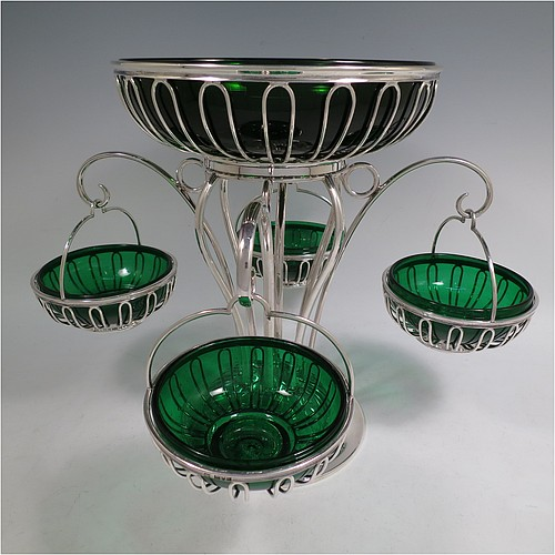 A very handsome and unusual Antique Edwardian Sterling Silver table Epergne centrepiece in an Art Nouveau style, having a removable central round wire-work basket and four matching removable swing baskets on side arms, all with dark green glass liners, and sitting on a spreading round base. Made by William Hutton of London in 1910. The dimensions of this fine hand-made antique silver Epergne table centrepiece are height 29 cms (11.5 inches), width across arms 38 cms (15 inches), and it weighs a total of approx. 1,954g (63 troy ounces)