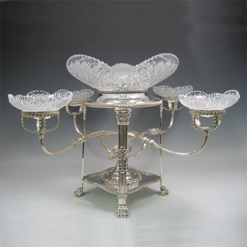 An Antique Victorian Silver-Plated table centre-piece epergne with five hand-cut crystal bowls, sitting in a Regency style frame with applied gadroon borders, swirl reeded arms, and all sitting on four lions paw feet. Made circa 1890. The dimensions of this fine hand-made antique silver plated epergne are height 38 cms (15 inches), and spread across bowls 58 cms (23 inches).