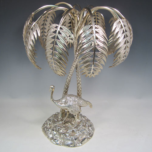 Antique Victorian silver-plated table centre-piece, having two palm trees inter-twined with a total of ten fronds, standing underneath which is a cast model of an ostrich, and all sitting on a round naturalistic cast rock base. Made in ca. 1880. The dimensions of this fine hand-made silver-plated table display are height 46 cms (18 inches), and spread 36 cms (14 inches).
