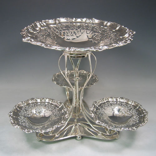 Sterling silver hand-pierced epergne, having four removable dishes, with one larger central dish, and three smaller dishes, all hand-pierced with applied shell and floral borders, sat in a wire-work frame on a spreading base with six ball feet. Made by Charles Widmer & Sons of Birmingham in 1912. Height 31 cms (12.25 inches), width 39.5 cms (15.5 inches). Total weight approx. 1,997g (64.4 troy ounces).