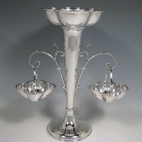 Sterling silver table epergne, having a central vase for flowers, with two removable hanging side baskets, with applied bead borders, and sitting on a pedestal foot. Made by William Hutton and Sons of Sheffield in 1923. Height 30 cms (11.75 inches), width 26 cms (10.25 inches). Total weight approx. 632g (20.4 troy ounces).