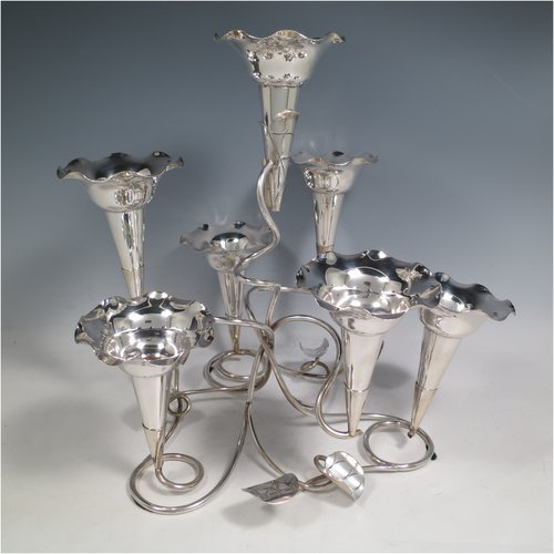 An Antique Victorian silver plated Art Nouveau flower vase epergne center-piece, having seven removable flower vases, with a tendril and leaf style body. All made in ca. 1890. The dimensions of this fine hand-made silver-plated flower epergne are height 30.5 cms (12 inches), and spread across vases 33 cms (13 inches).