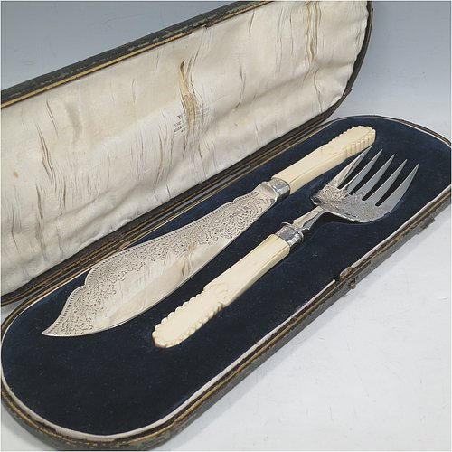 An Antique Victorian Sterling Silver fish serving knife and fork set, having hand-carved bone or ivory handles, with hand-engraved blade and tines with floral decoration, all in their original satin and blue velvet-lined presentation box. Made by James Deakin & Sons of Sheffield in 1887. The dimensions of this fine hand-made antique silver fish serving set are length of knife 31 cms (12.25 inches), and length of fork 24 cms (9.5 inches). Please note that the cream coloured satin upper lining to the lid is slightly damaged.
