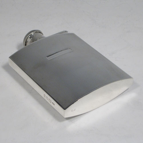 Sterling silver Art Deco style whisky flask, having a rectangular body with engine-turned engraved decoration, plain flat shoulders and sides, and a hinged and bayonet-fit lid with knurled top, and a vacant recessed cartouche on oe side. Made by Carrington and Co., of London in 1934. The dimensions of this fine hand-made silver whisky hip flask are length 11 cms (4.3 inches), width 8 cms (3 inches), depth 2.5 cms (1 inch), and it weighs approx. 148g (4.8 troy ounces).