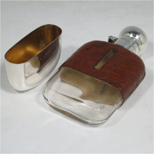 A Sterling Silver and glass whisky flask, with crocodile leather skin mount, and a sight level both sides, having a bayonet fit lid and a pull-off cup with gold-gilt interior. Made by W. C. Griffiths of Birmingham in 1924. The dimensions of this fine hand-made silver and glass whisky flask are length 12 cms (4.75 inches), width 6 cms (2.3 inches), and depth 2.5 cms (1 inch).