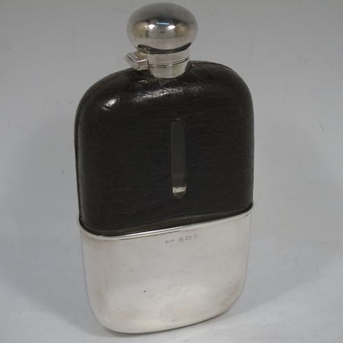 A large and handsome Antique Victorian Sterling Silver and glass whisky flask, with crocodile leather skin mount, and a sight level both sides, having a bayonet fit lid and a pull-off cup with gold-gilt interior. Made in Birmingham in 1900. The dimensions of this fine hand-made antique silver and glass whisky flask are length 18 cms (7 inches), width 9.5 cms (3.75 inches), and depth 4 cms (1.5 inches). Please note slight damage to crocodile skin cover on one side.