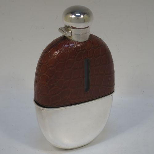A large and handsome Antique Sterling Silver and glass whisky flask, with crocodile leather skin mount, and a sight level both sides, having an oval shaped main body, a hinged bayonet fit lid and a pull-off cup with gold-gilt interior. Made by W. C. Griffiths of Birmingham in 1911. The dimensions of this fine hand-made antique silver and glass whisky flask are length 16 cms (6.25 inches), width 9 cms (3.5 inches), and depth 3.5 cms (1.3 inches). Please note that the glass neck has a small chip, but we have made sure that it has been ground down properly, so it is not sharp in any way, and does not get in the way of drinking.