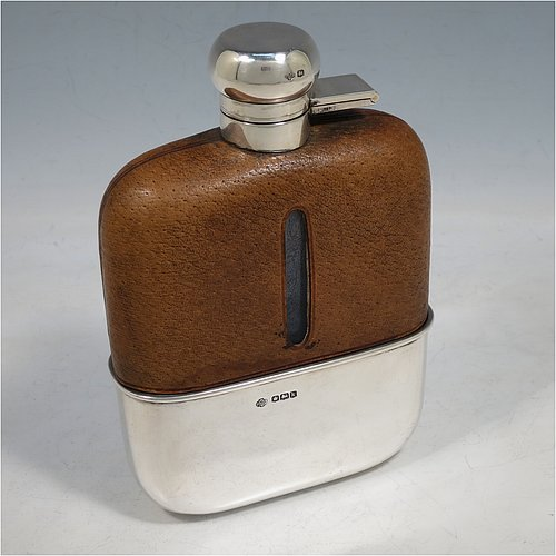 A large Sterling Silver and glass whisky flask, with leather skin mount, and a sight level both sides, having a bayonet fit lid and a pull-off cup with gold-gilt interior. Made by William Hutton & Sons of Sheffield in 1927. The dimensions of this fine hand-made silver and glass whisky flask are length 17 cms (6.75 inches), width 11.5 cms (4.5 inches), and depth 4 cms (1.5 inches).