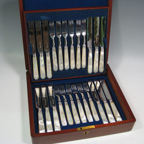 Antique Victorian sterling silver and mother-of-pearl handled fruit set for 12 people. Having plain parallel bladed knives and plain four-prong forks, reeded ferrules connecting the mother-of-pearl handles, and fitted into an original oak canteen with removable top tray and blue velvet interior. Made by Thomas Prime and Sons of Birmingham between 1865 and 1870. Length of knife 20 cms (8 inches), length of fork 17 cms (6.75 inches)