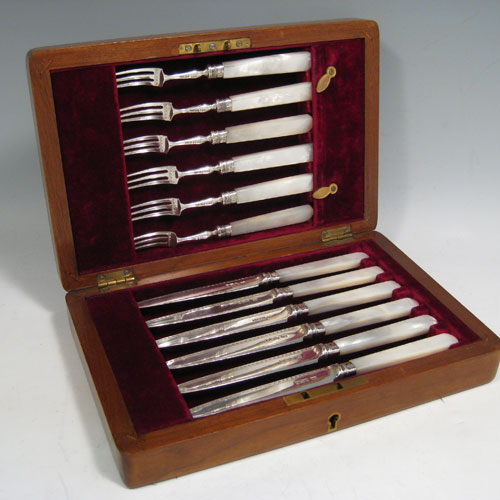 Antique sterling silver and mother-of-pearl handled fruit set for six people. Having engraved tapering bladed knives and three-prong forks, beaded ferrules connecting the mother-of-pearl handles, and fitted into an original oak canteen with maroon velvet interior. Made by George Heath of Sheffield in 1911. Length of knife 19 cms (7.5 inches), length of fork 15 cms (6 inches)