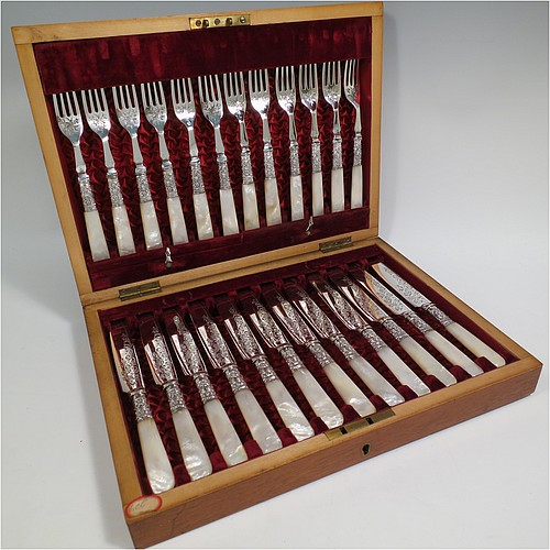 An Antique Victorian silver-plated and mother-of-pearl handled fruit set for twelve people, having hand-engraved tapering bladed knives and four-prong forks with floral decoration, with large hand-chased silver ferrules connecting the mother-of-pearl handles, all fitted into their original maroon satin and velvet-lined presentation box. The ferrules are of hallmarked sterling silver and are made by John Sanderson of Sheffield in 1897. The dimensions of this fine hand-made antique silver fruit service are length of knife 21 cms (8.25 inches), and the length of the fork 17.5 cms (7 inches).