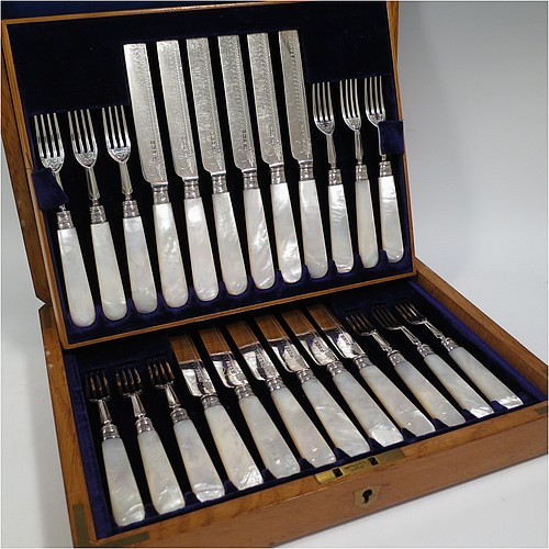 An Antique Edwardian Sterling Silver and mother-of-pearl handled fruit set for twelve people. Having straight-sided rounded-end blade knives, and four-prong forks, with hand-engraved floral decoration, and reed-work ferrules, all fitted into an original presentation box with dark blue velvet interior. Made by George Hancock of Sheffield in 1908. The dimensions of this fine hand-made antique silver fruit service are length of knife 19 cms (7.5 inches), and the length of the fork 15 cms (6 inches).