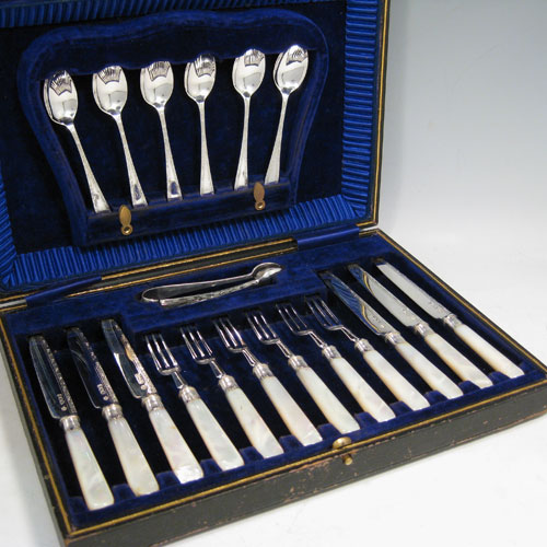 Antique Edwardian sterling silver and mother-of-pearl handled fruit set for six people. Having engraved tapering bladed knives and three-prong forks, reeded ferrules connecting the mother-of-pearl handles, together with a matching set of six teaspoons and a pair of sugar tongs, all fitted into an original presentation box with blue velvet interior. Made by William Hutton of London in 1907. The dimensions of this fine hand-made silver fruit service are length of knife 16 cms (6.3 inches), and the length of the fork 14 cms (5.5 inches).