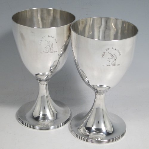 Antique Georgian sterling silver pair of goblets, having plain round bodies, and sitting on pedestal feet with reeded borders. Made by Henry Chawner of London in 1793/94. The dimensions of this fine hand-made pair of silver goblets are height 15 cms (6 inches), diameter at top 8 cms (3.25 inches), and the total weight is approx. 335g (10.8 troy ounces). Please note that both goblets are engraved with crests.