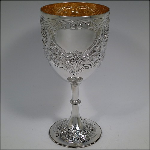 A large Antique Victorian Sterling Silver goblet, having a round tapering body with hand-chased floral and scroll decoration, two plain oval shaped cartouches either side, a gold-gilt interior, and all sitting on a pedestal foot with matching decoration and a bead border. Made by Angel and Savory of London in 1891. The dimensions of this fine hand-made antique silver goblet are height 22 cms (8.75 inches), diameter at lip 10 cms (4 inches), and it weighs approx. 303g (9.8 troy ounces).