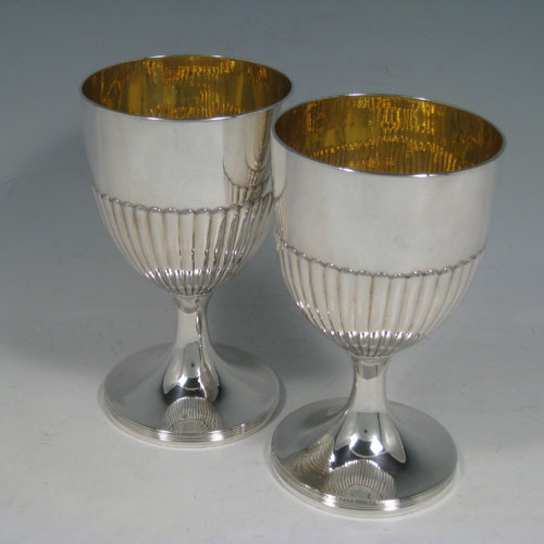 Antique Georgian sterling silver pair of goblets, having round bodies with hand-chased half-fluted decoration, gold-gilt interiors, and sitting on pedestal feet with reeded borders. Made by John Robins of London in 1803. The dimensions of this fine hand-made pair of silver goblets are height 16 cms (6.3 inches), diameter at top 9 cms (3.5 inches), and the total weight is approx. 517g (16.7 troy ounces).