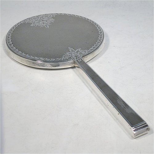 A Sterling Silver hand-mirror, having a round body and a square cross-section handle, with engine-turned decoration and a very pretty hand-engraved floral border, and an original round bevelled mirror. Made by Broadway & Co., of Birmingham in 1971. The dimensions of this fine hand-made silver hand mirror are length 25.5 cms (10 inches), and diameter of mirror 12.5 cms (5 inches).