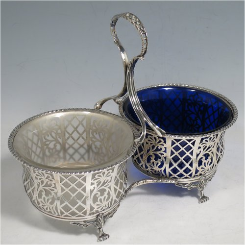 An Antique Edwardian Sterling Silver preserve, jam and honey pot holder, having a blue and frosted glass pot, sitting in a hand-pierced frame with floral and geometric decoration, with applied gadroon borders, a reeded and pierced loop handle, and all sitting on four cast floral feet. Made by Mappin and Webb of London in 1907. The dimensions of this fine hand-made antique silver and glass preserve holder are length 21 cms (8.25 inches), width 11 cms (4.25 inches), height 17.5 cms (7 inches),  and it weighs approx. 243g (7.8 troy ounces).