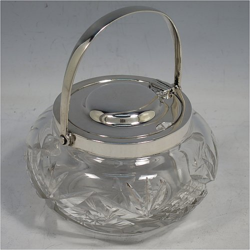 A Sterling Silver and crystal honey or jam jar, having a round bellied body with hand-cut geometrical design and a star-cut base, a plain round mount, with a mechanical swing-handled hinged and domed lid. Made by Hukin & Heath of Birminghamn in 1928. The dimensions of this fine hand-made silver and glass conserve jar are height (inc. handle) 12.5 cms (5 inches), and diameter 11 cms (4.3 inches).