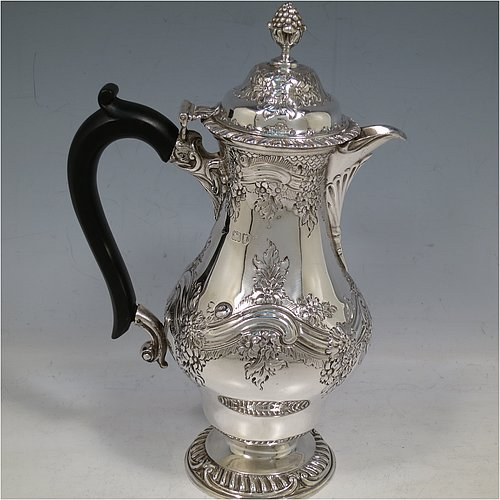 An Antique Victorian Sterling Silver hot water / milk pot, having a round bellied body, with hand-chased floral & scroll decoration and applied gadroon borders, with an ebonised wooden scroll handle and a hinged lid with a cast pineapple finial, and sitting on a pedestal foot. Made by Goldsmiths & Silversmiths of London in 1901. The dimensions of this fine hand-made antique silver serving pot are height 24 cms (9.5 inches), length 15 cms (6 inches), and it weighs approx. 600g (19 troy ounces).