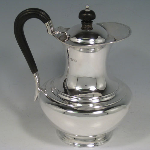 Antique Edwardian sterling silver hot water / milk pot, having a plain round baluster body, reeded borders, ebonised wooden scroll handle and finial, hinged lid, and sitting on a pedestal foot. Made by Henry Atkins of Sheffield in 1909. The dimensions of this fine hand-made silver serving pot are height 19 cms (7.5 inches), length 15 cms (6 inches), and it weighs approx. 400g (13 troy ounces).