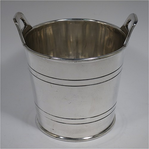 An Antique Edwardian silver plated ice bucket, having a plain round body with tapering straight sides and hand-chased reeded decoration, an internal removable dry ice drainer, with two top cast side handles, and all sitting on a flat base. Made by Collins of London in ca. 1910. The dimensions of this fine hand-made antique silver-plated ice bucket are height 15.5 cms (6 inches), and diameter at lip 14 cms (5.5 inches).