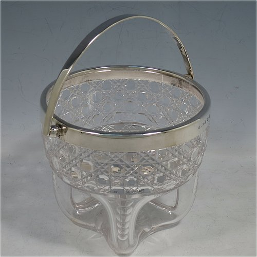 An Antique Victorian Sterling Silver and hand-cut crystal ice bucket, having a round hob-nail cut crystal body sitting on four unusual conjoined legs, with an internal removable dry ice drainer, a plain silver rim, and a hinged swing handle. Made by the Henry Williamson Ltd., of Birmingham in 1900. The dimensions of this fine hand-made antique silver and crystal ice bucket are height (excluding handle) 12.5 cms (5 inches), and diameter at lip 12.5 cms (5 inches).