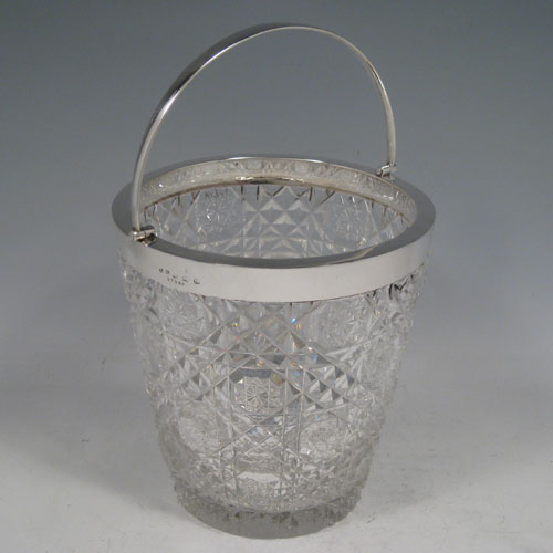 Sterling silver and hand-cut crystal ice bucket with swing-handle and removable strainer base. Made by John Grinsell of Birmingham in 1913. Height (inc. handle) 21.5 cms (8.5 inches), diameter 13.5 cms (5.25 inches).
