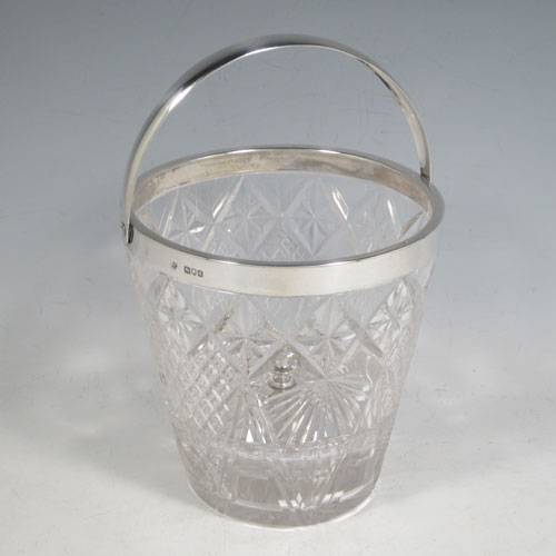 Antique Victorian sterling silver ice bucket, having a round hand-cut crystal body with tapering sides, an internal removable dry ice drainer, a plain silver rim, and a hinged swing handle. Made by the Dixon Brothers of London in 1899. The dimensions of this fine hand-made silver ice bucket are height (excluding handle) 13 cms (5 inches), and diameter at lip 13 cms (5 inches). Please note that there is a small crack in the top border that is hidden by the silver rim.