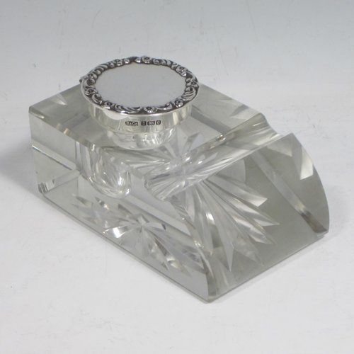 Antique Edwardian sterling silver and hand-cut crystal inkstand, having a rectangular body with chamfered corners, a pen holder groove above a curved front face, plain round silver mount with a hinged lid having an applied floral border, and all sitting on a star-cut flat base. Made by Broadway & Co., of Birmingham in 1904. The dimensions of this fine hand-made silver and crystal inkstand are height 5 cms (2 inches), length 10 cms (4 inches), and width 6.5 cms (2.5 inches).