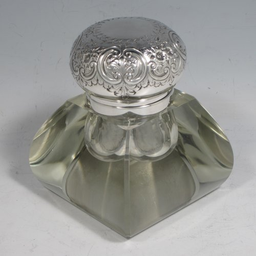 An Antique Victorian sterling silver and hand-cut crystal inkstand, having a square baluster body with rounded faces and chamfered corners, a plain round silver mount with a hinged lid having hand-chased floral and scroll decoration, and all sitting on plain cut flat base. Made by the Deakin Brothers of Sheffield in 1898. The dimensions of this fine hand-made silver and crystal inkstand are height 11 cms (4.25 inches), and 9 cms (3.5 inches) square.