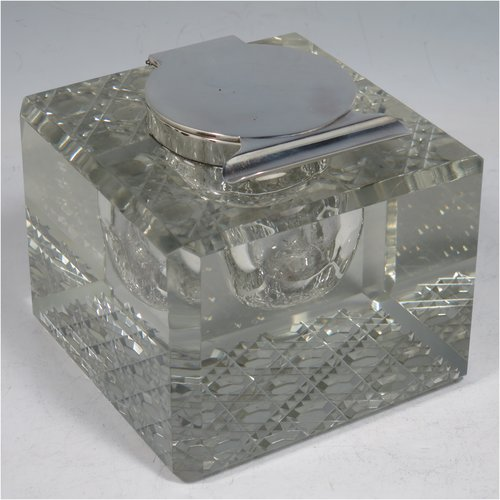 An Antique Edwardian Sterling Silver and hand-cut crystal inkstand, having a square body with chamfered corners, a plain round silver mount with a hinged lid and an unusual attached pen holder, and all sitting on a hand-cut hobnail pattern flat base. Made by Finnigans Ltd., of Birmingham in 1902. The dimensions of this fine hand-made antique silver and crystal inkstand are height 9 cms (3.5 inches), and 10 cms (4 inches) square.