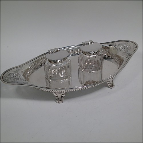 An Antique Edwardian Sterling Silver two bottle double inkstand, with an oval boat-shaped body, having a hand-pierced gallery border and hand-engraved ends with neoclassical style engraving, two removable cut-crystal ink bottles with hinged lids, and all sitting on four cast flanged feet. Made by Hawksworth and Eyre of Sheffield in 1902. The dimensions of this fine hand-made antique sterling silver double inkstand are length 28 cms (11 inches), width 14 cms (5.5 inches), and it weighs approx. 350g (11.2 troy ounces).