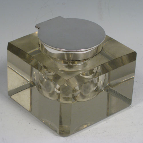 An Antique Victorian Sterling Silver and hand-cut crystal inkstand paper weight, having a square body with chamfered upper edges, a plain round mount and a flat-topped hinged lid, and with a removable glass liner, all sitting on a flat-cut plain base. Made by John Grinsell and Sons of London in 1898. The dimensions of this fine antique silver and crystal inkstand are height 7 cms (2.75 inches), and 9 cms (3.5 inches) square.