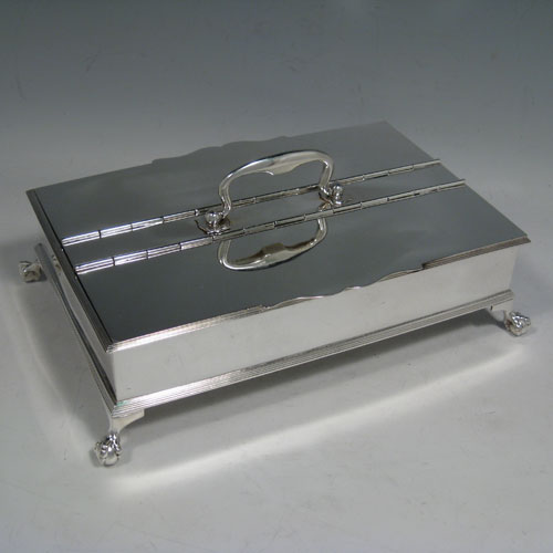 Sterling silver Treasury inkstand, having a rectanuglar body, with two hinged lids covering two compartments, with one side containing two crystal and silver inkwells, a cast scroll carrying handle, and all sitting on four cast claw and ball feet. Made by the Barnard Brothers of London in 1913. Length 25 cms (9.75 inches), height 9 cms (3.5 inches), width 16.5 cms (6.5 inches). Total weight approx. 1,354g (43.7 ounces).