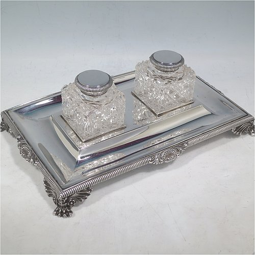 An Antique Victorian Sterling Silver inkstand, having a rectangular body with gadroon and shell border, two square hand-cut crystal removable ink bottles with round hinged lids, all sitting on four cast foliate and claw feet. Made by Henry Wilkinson & Co., of London in 1899. The dimensions of this fine hand-made antique silver double inkstand are length 25 cms (10 inches), width 16 cms (6.3 inches), height 8 cms (3.25 inches), and it weighs approx. 395g (12.6 troy ounces).