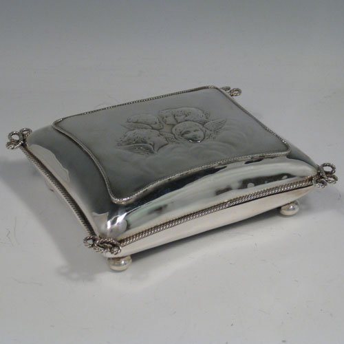 Antique Edwardian sterling silver very unusual hand-made jewellery box with hand-chased cherubs and applied rope-twist border, sitting on cushion-ball feet. Lined with maroon velvet. All made by William Comyns of London in 1906. Length 15 cms, height 4.5 cms.