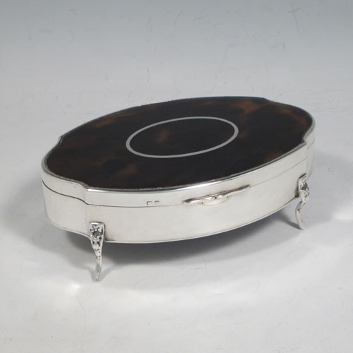 Sterling silver and tortoise-shell jewelery box, having an oval-shaped plain body, a hinged lid with inlaid cartouche, a light brown velvet-lined interior, and sitting on four foliate feet. Made in Birmingham in 1920. The dimensions of this fine hand-made silver and tortoise-shell jewelery box are length 13 cms (5 inches), width 9 cms (3.5 inches), and height 4.5 cms (1.75 inches)