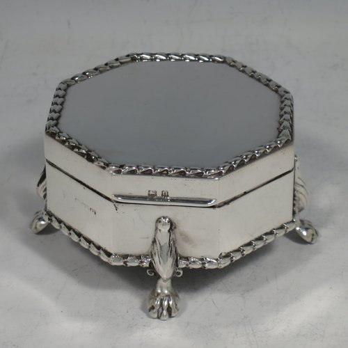 An Antique Sterling Silver jewellery box, having a plain hexagonal shaped body,, a hinged lid, with applied gadroon borders, an original cream coloured satin-lined base, and all sitting on four cast lions-paw feet. Made in Birmingham in 1912. The dimensions of this fine hand-made silver jewelery box are width 7 cms (2.75 inches), and height 4.5 cms (1.75 inches), and it weighs approx. 110g (3.5 troy ounces). Please note that the liner is removable.