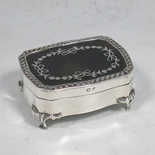 A very pretty Antique Edwardian Sterling Silver and tortoise-shell jewellery box, having a shaped rectangular body, a tortoise-shell hinged lid with in-laid flowers and ribbon bows, an applied gadroon border, a dark blue velvet-lined interior, and sitting on four cast foliate legs. Made by Henry Miller of Birmingham in 1910. The dimensions of this fine hand-made antique silver and tortoise-shell jewelery box are length 7 cms (2.75 inches), width 5.5 cms (2.25 inches), and height 3 cms (1.25 inches).